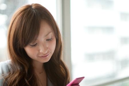 携帯電話でメールを打つ美人女性
